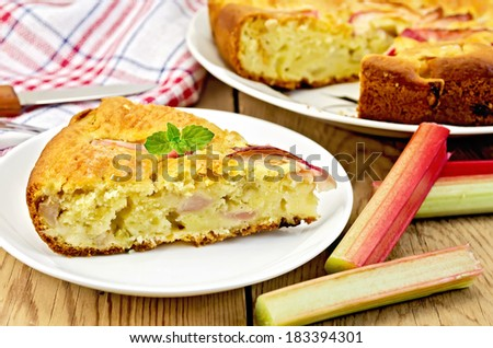 Piece of sweet cake with rhubarb, mint, napkin, knife on background wooden plank