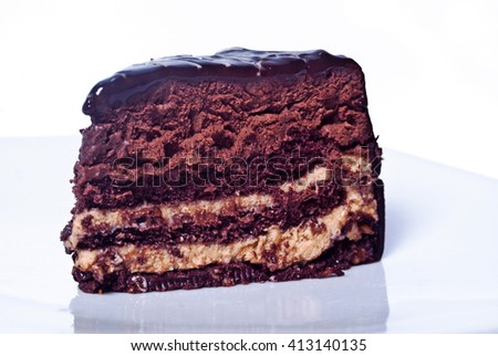 Piece of sweet chocolate cake isolated on white background. Selective focus with shallow depth of field