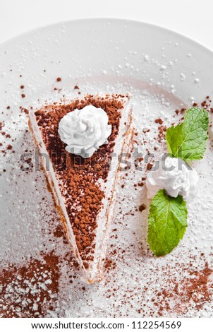 piece of tiramisu on white plate decotated with cacao and mint - stock photo