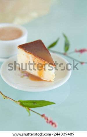 Piece of toffee cheesecake with crashed biscuits and caramel  on the top. Cheesecake was prepared with flour, white cheese, sugar, eggs and butter. Presented on white plate with silver knife. - stock photo