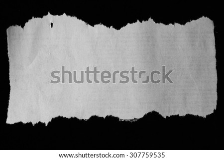 Piece of torn paper on black - stock photo