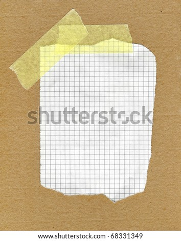 piece of torn squared paper stuck with tape - stock photo