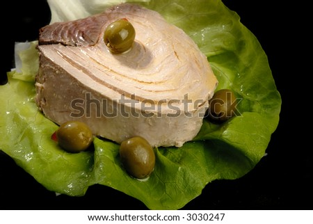 Piece of tuna on a salad lief and olive on it pictured on a dark background