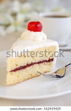 Piece of white cake with vanilla frosting and raspberry jelly, topped with cherry.