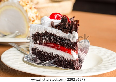 Piece of white cream cake chocolate and cherry topping on white dish - stock photo