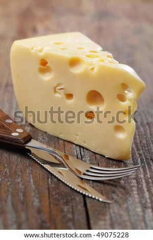 Piece of yellow cheese with big holes - stock photo