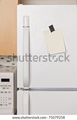 Piece of yellow paper taped to a refrigerator door - stock photo