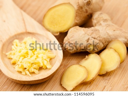 Piece slice and crushed of ginger against a wood worktop - stock photo