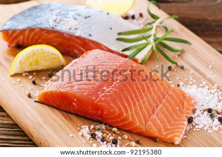 pieces if fresh salmon on the wooden board - stock photo