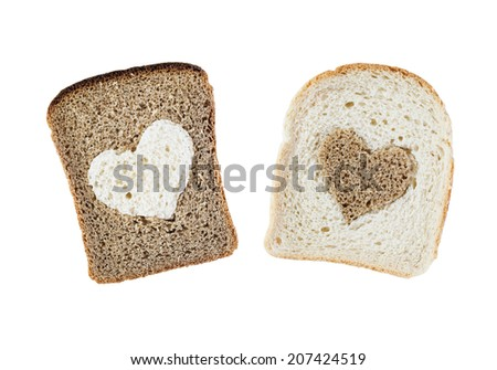 Pieces of black and white bread with silhouettes of a heart isolated over white