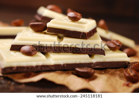 pieces of black and white coffee chocolate bar with seeds on wooden table - stock photo
