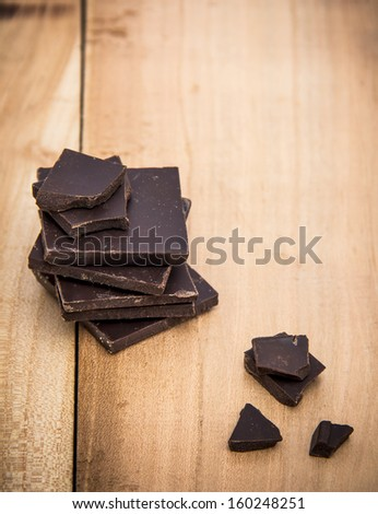 Pieces of black chocolate in a stack along with a small pieces on the old wooden table