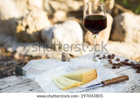 Pieces of cheese and raisins with a red wine glass on a old wooden board in the countryside. A rustic lunch with Idiazabal cheese cut and wine  - stock photo