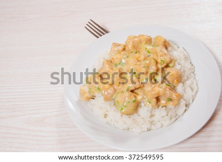 pieces of chicken fillet and cheese sauce with rice