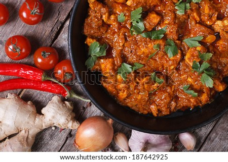 pieces of chicken fillet in curry sauce ingredients in a pan with the old table top view close-up horizontal  - stock photo