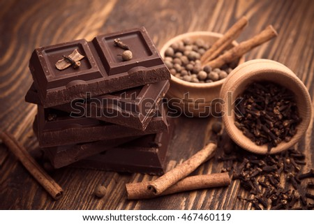 Pieces of chocolate and spices on wooden table