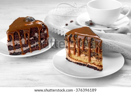 Pieces of chocolate cake with caramel on wooden table closeup
