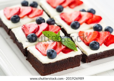 Pieces of chocolate cake with icing, strawberry, blueberry and mint on a plate
