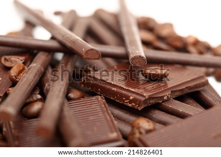 Pieces of chocolate, coffee beans and chocolate sticks.