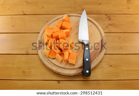 Pieces of chopped butternut squash with a sharp kitchen knife on a wooden cutting board  - stock photo