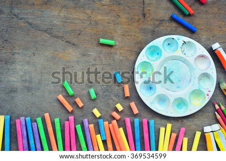 pieces of color chalk scattered with palette on wooden floor.