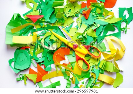 Pieces of colored paper and yellow  scissors. Pieces of colored paper that sliced baby - stock photo