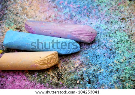 Pieces of colorful chalk on the painted pavement - stock photo
