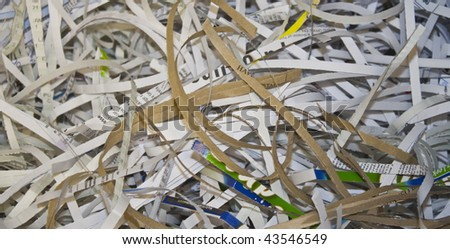 pieces of confidential paperwork, shredded to help protect against identity theft - stock photo