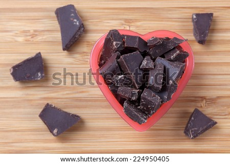 Pieces of dark chocolate in a heart bowl. Close-up. - stock photo