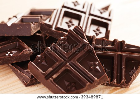 Pieces of dark chocolate on a wooden table, closeup shot, selective focus - stock photo
