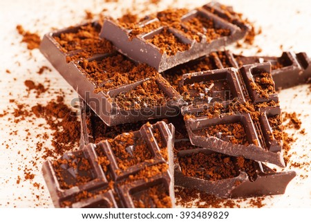 Pieces of dark chocolate on a wooden table with cacao powder, closeup shot, selective focus - stock photo
