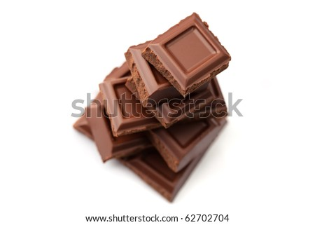 Pieces of dark chocolate stacked, shallow dof, isolated on white.