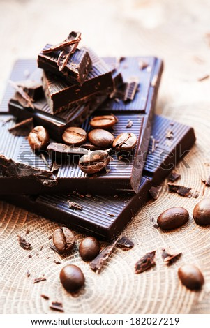Pieces of dark chocolate with a coffee beanes on a wooden background