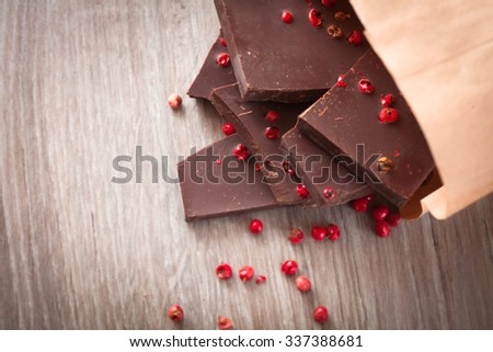Pieces of dark chocolate with pink pepper on the table