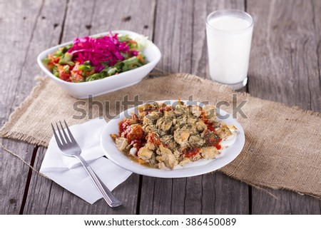 pieces of delicious fried chicken with salad and ayran on a white plate - stock photo