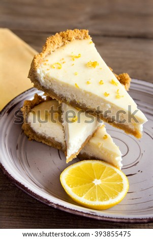 Pieces of delicious homemade lemon cheesecake on plate close up - stock photo