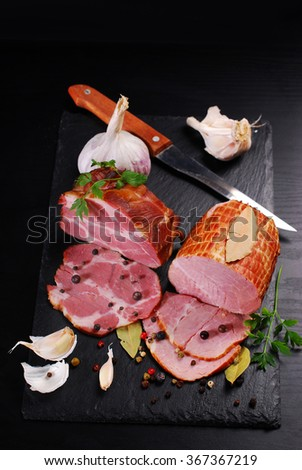 pieces of delicious homemade smoked pork ham with spices on black background - stock photo