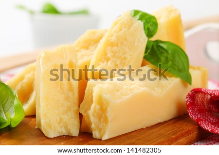 Pieces of delicious parmesan cheese on a wooden cutting board - stock photo
