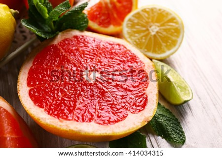 Pieces of different citrus fruit on light wooden table - stock photo