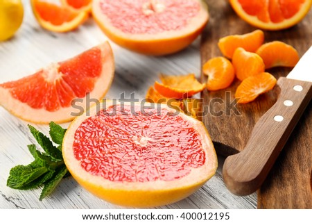Pieces of different citrus fruit on wooden cutting board - stock photo