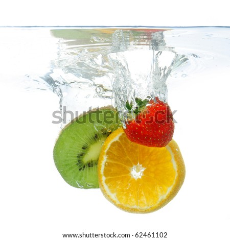 Pieces of different fruit dropped in water, isolated on white - stock photo