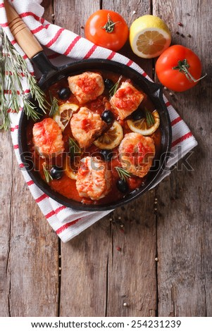 Pieces of fish in tomato sauce with olives and lemon in a frying pan. vertical top view - stock photo