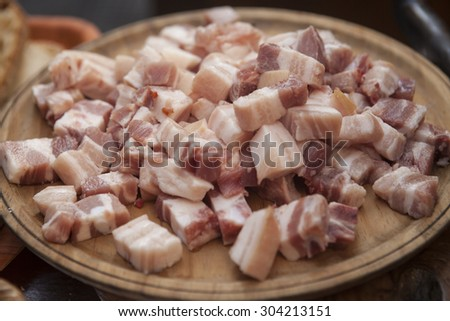 Pieces of fresh bacon on the plate - stock photo