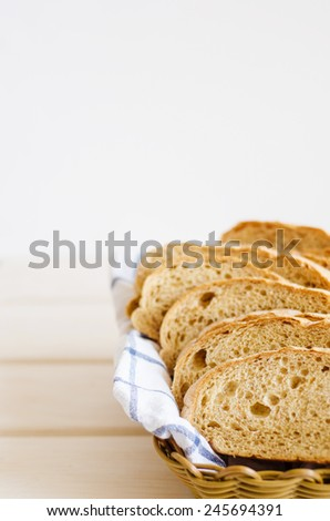 pieces of fresh homemade bread on a white towel in a basket - stock photo