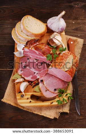 pieces of fresh homemade smoked ham with spices and bread on rural background - stock photo