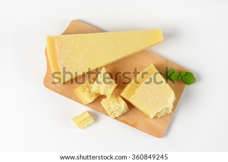 pieces of fresh parmesan cheese on wooden cutting board - stock photo