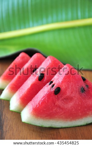 Pieces of fresh watermelon on wooden board with banana leaf on background - stock photo