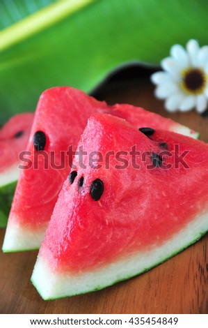Pieces of fresh watermelon with banana leaf on background - stock photo