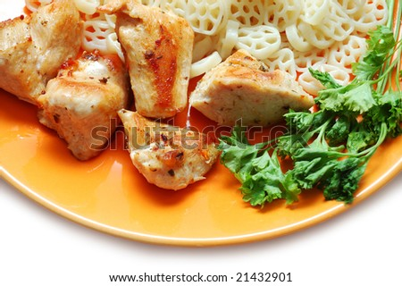 Pieces of fried chicken, pasta and parsley on orange plate - stock photo