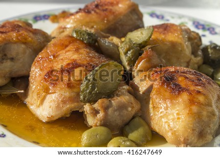 Pieces of fried chicken, pickles, olives on a large plate. - stock photo